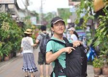 Borsa maschio della macchina fotografica di apertura di viaggiatore con zaino e sacco a pelo sulla via Immagine Stock