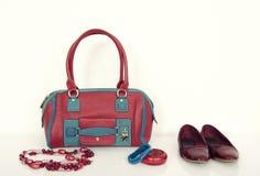 Borsa rossa e blu con la collana, i braccialetti e gli appartamenti di corrispondenza Immagine Stock