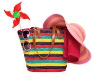 Borsa a strisce variopinta della spiaggia con gli occhiali da sole di paglia di un asciugamano del cappello e immagine stock libera da diritti