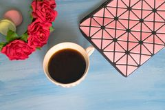 Borsa, tazza di caffè, rose e maccheroni cosmetici su fondo blu immagine stock libera da diritti