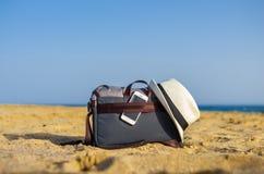 Borsa a tracolla con uno smartphone e un cappello bianco sulla sabbia della spiaggia fotografia stock