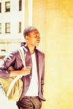Borsa a tracolla di trasporto del giovane uomo afroamericano, viaggiante nella N Immagini Stock Libere da Diritti