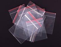 Borsa trasparente di plastica della chiusura lampo su fondo nero Imballaggio della serratura dello zip del blocco Involucro sigil immagine stock libera da diritti