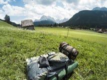 Borsa turistica con una tenda e un sacco a pelo in erba verde con i moutains delle dolomia su un backgroun e le casette in a Fotografia Stock Libera da Diritti