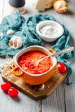 Borsch, beetroot soup. Traditional soup of Russian and Ukrainian cuisine borsch. Meat soup with beets in an orange bowl on a light wooden background stock image