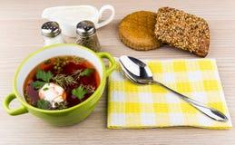 Borsch, bread, spices, spoon on napkin and sour cream. On table stock photos