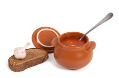 Borsch in clay pot with bread and garlic Stock Image