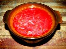 Borsch de la porción en un pote de arcilla en un tablero de madera Foto de archivo