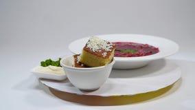 Borsch i platta med den wood skeden och svart bröd som isoleras på vit Grönsaker och kött i röd rödbetasoppa eller borsch lager videofilmer