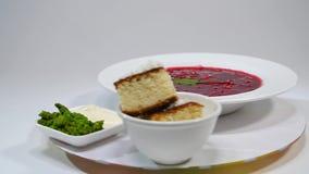 Borsch in piatto con il cucchiaio di legno ed il pane nero isolati su bianco Verdure e carne in zuppa di barbabietola o borsch ro stock footage