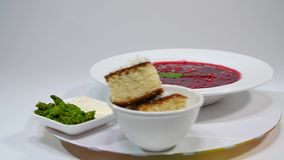 Borsch in plate with wood spoon and black bread isolated on white. Vegetables and meat in red beetroot soup or borsch. With sour cream. bread, green onion stock footage
