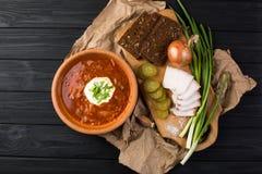 Borsch soup on the dark wood table. Ukrainian borsch soup and garlic buns on the table royalty free stock photos