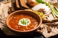 Borsch soup on the dark wood table. Ukrainian borsch with sour cream and garlic buns on the table stock photo