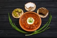 Borsch soup on the dark wood table. Ukrainian borsch with sour cream and garlic buns on the table royalty free stock photo