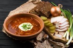 Borsch soup on the dark wood table. Ukrainian borsch with sour cream and garlic buns on the table stock photos