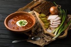 Borsch soup on the dark wood table. Ukrainian borsch with sour cream and garlic buns on the table stock image