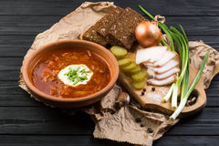 Borsch soup on the dark wood table. Ukrainian borsch with sour cream and garlic buns on the table royalty free stock photography