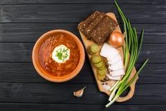 Borsch soup on the dark wood table. Ukrainian borsch with sour cream and garlic buns on the table stock photography