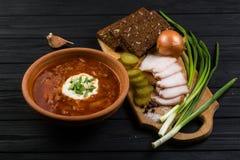 Borsch soup on the dark wood table. Ukrainian borsch with sour cream and garlic buns on the table stock images