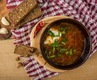 Borsch-soup with sour cream and bread. Top view. Tasty and nutritious borsch-soup with meat, potatoes, cabbage, tomatoes, beans, sour cream, parsley, onion royalty free stock image