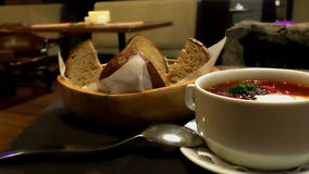 Borsch on the table close up with baked bread. Panorama of the very tasty soup with bread stock video