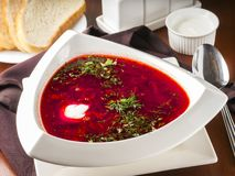 Borsch. Ucrainian russian traditional beetroot soup - borsch in triangular white plate on dark brown wooden table in restaurant stock photography