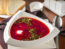 Borsch. Ucrainian russian traditional beetroot soup - borsch in triangular white plate on dark brown wooden table in restaurant stock photos