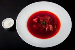 Borsch - une soupe des betteraves dans une cuvette de poterie de terre sur un chiffre, une pierre ou le fond en métal, un plat uk photo libre de droits