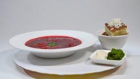 Borsch vermelha com carne na placa Um borscht vermelho delicioso com creme de leite e ervas em uma placa branca Ucraniano tradici Imagens de Stock