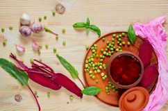 Borscht casalingo con le verdure sui precedenti di legno decorati con la barbabietola affettata fresca, l'aglio ed i piselli Immagini Stock Libere da Diritti