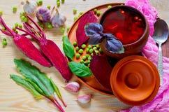 Borscht casalingo con le verdure sui precedenti di legno con la barbabietola affettata fresca, l'aglio, le foglie del basilico ed Immagine Stock Libera da Diritti
