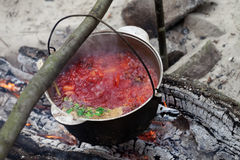 Borscht cooking in sooty cauldron on campfire. Borscht (Ukrainian traditional soup) cooking in sooty cauldron on campfire at forest Stock Photos