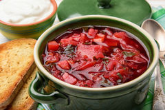 Borscht - traditional russian and ukrainian beetroot soup in green ceramic pot on wooden background. Stock Photography