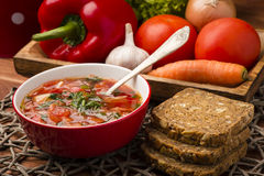Borscht - traditional russian and ukranian beetroot soup in red bowl on wooden background. Stock Images