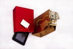 Borse del regalo con la compressa ed i dollari Fotografia Stock