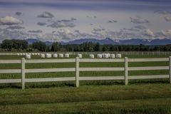 Borse della balla con il recinto e la montagna bianchi Backgroundn immagine stock libera da diritti