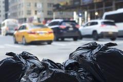 Borse di rifiuti con traffico confuso nel fondo in environmen urbani Fotografie Stock