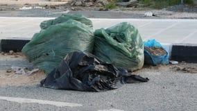 Borse di rifiuti di plastica piene sulla via Sprechi e ricicli il concetto Movimento lento video d archivio
