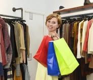 Borse di trasporto della giovane donna che comperano al boutique di modo che sceglie sorridere dei vestiti felice fotografie stock