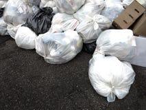Borse e rifiuti di immondizia accatastati su sulla via Fotografia Stock Libera da Diritti