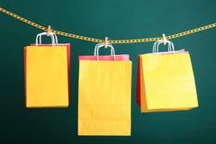 Borse gialle di compera del regalo su fondo verde Immagini Stock Libere da Diritti