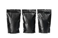 Borse nere di caffè su un fondo bianco Fotografia Stock