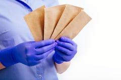 Borse per la sterilizzazione degli strumenti nelle mani placcate in guanti sterili fotografie stock libere da diritti