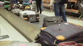 Borse, valigie che girano su un nastro trasportatore all'aeroporto Reclamo di bagaglio stock footage