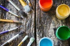 Borsta för att måla och måla gouachen i en halvcirkel på den gamla trätabellen Royaltyfri Bild