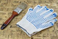 Borsta med blåa handskar på en trätabell Arkivbild