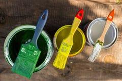 Borsta och kunna med målarfärg för gul gräsplan och vit royaltyfria foton