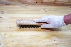 Borstaprocessen av tr?plankan Den manliga handen rymmer att borsta spelrum med lampa royaltyfri fotografi