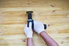 Borstaprocessen av tr?plankan Den manliga handen rymmer elektriskt rotera f?r borsta maskin med borstemetallskivan som sandpappra royaltyfria foton