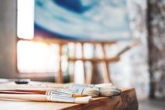 Borstar av konstnärnärbilden på en trätabell i studion Bakgrundskanfas på staffli Målareseminarium Arkivbilder